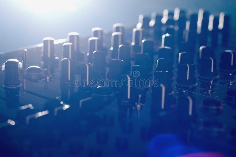 Le mélangeur audio du DJ avec la lumière latérale et la lentille évasent image libre de droits