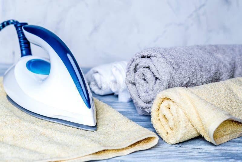 Le ménage a placé avec les serviettes et le fer sur le fond de blanchisserie photo libre de droits