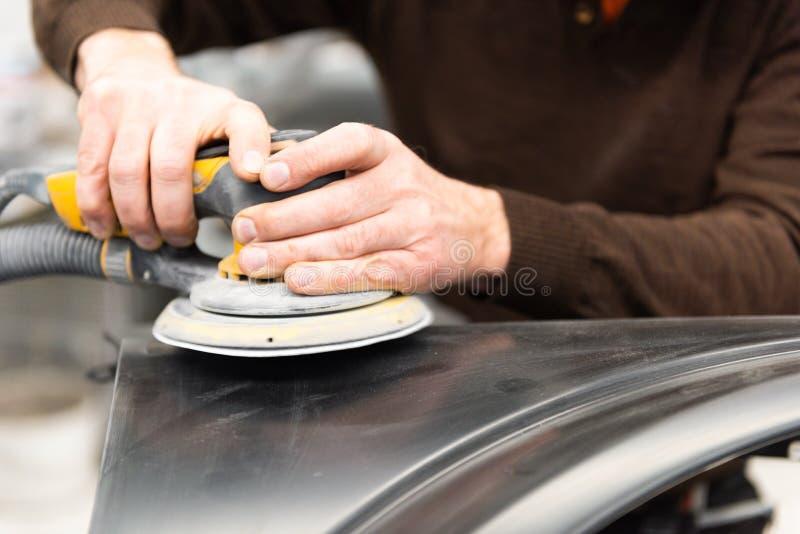 Le m?canicien de voiture rectifie une pi?ce de voiture en travail manuel dans une station service - atelier de r?paration de voit photo stock