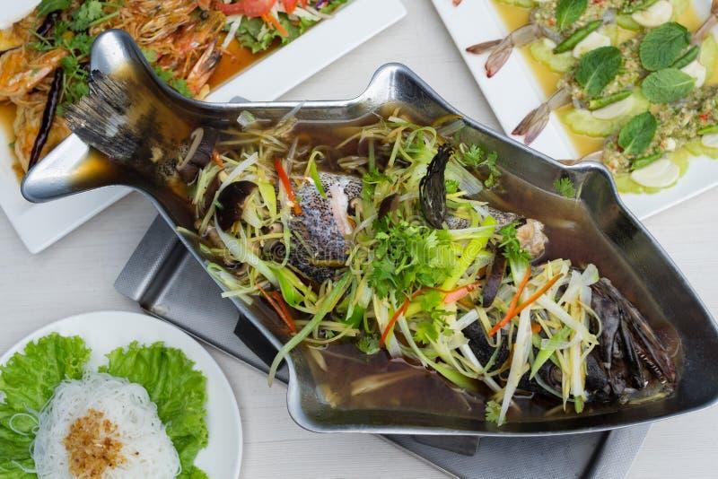 Le m?rou cuit ? la vapeur avec la sauce de soja dans les poissons forment le pot sur la table avec l'autre nourriture photographie stock libre de droits