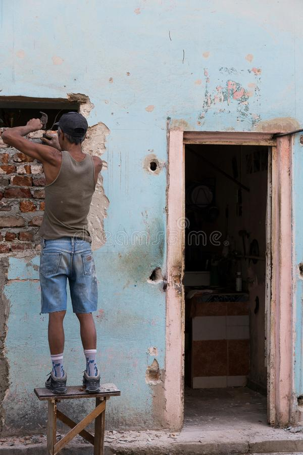 Le maçon cubain travaillant au vieux pastel de diminution des effectifs a coloré le logement photographie stock