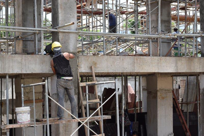 Le maçon de construction de bâtiments faisant plâtrant le travail se tenant sur l'échafaudage siffle au chantier image libre de droits