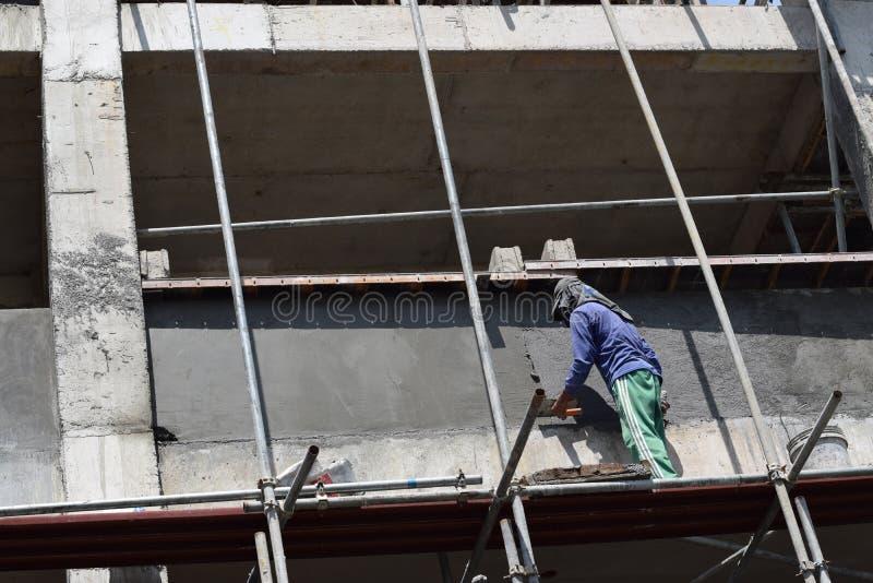 Le maçon philippin de construction plâtrant le coulis à bord de l'échafaudage siffle sur seul le gratte-ciel photographie stock