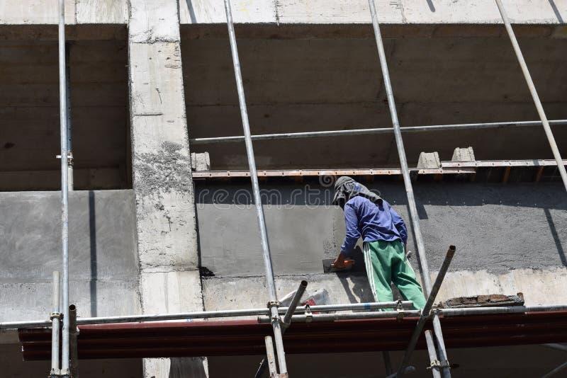 Le maçon philippin de construction plâtrant le coulis à bord de l'échafaudage siffle sur seul le gratte-ciel images libres de droits