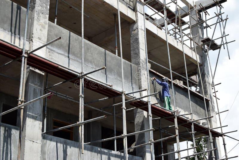 Le maçon philippin de construction plâtrant le coulis à bord de l'échafaudage siffle sur seul le gratte-ciel image libre de droits
