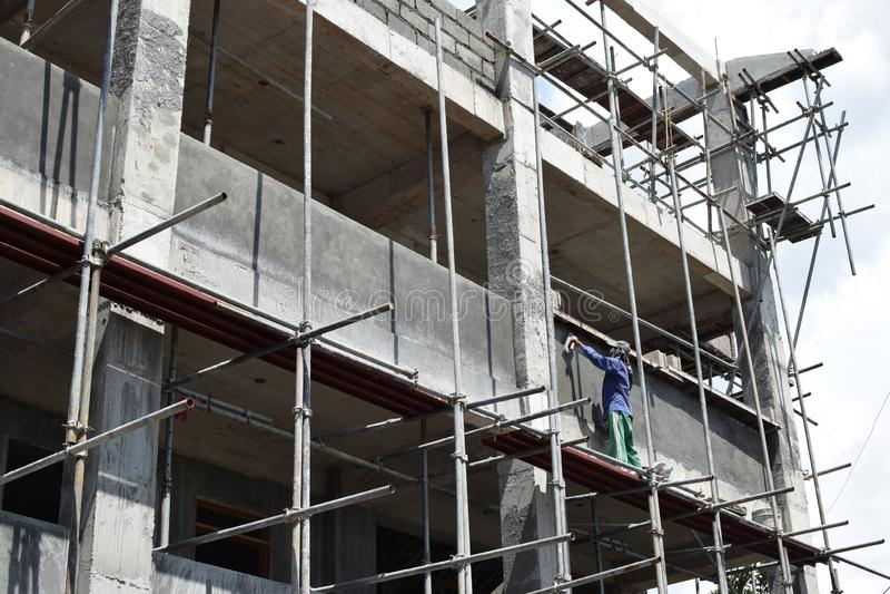 Le maçon philippin de construction plâtrant le coulis à bord de l'échafaudage siffle sur seul le gratte-ciel photos libres de droits