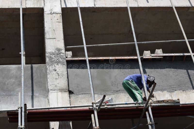 Le maçon philippin de construction plâtrant le coulis à bord de l'échafaudage siffle sur seul le gratte-ciel photo libre de droits