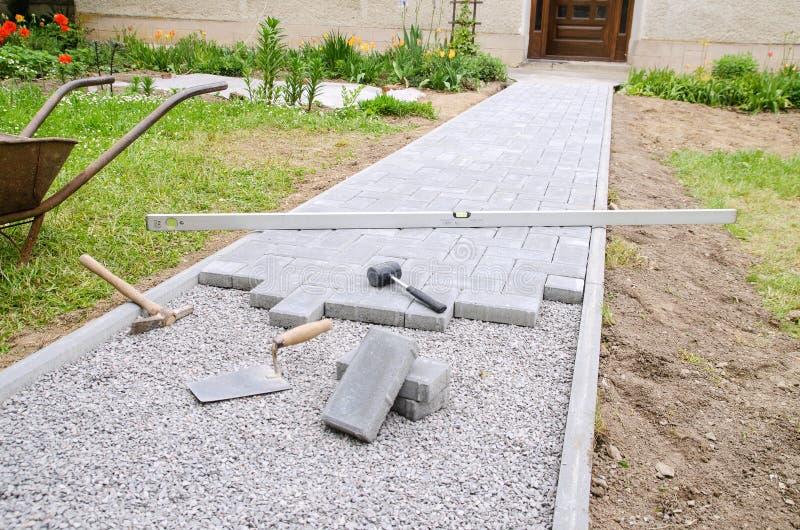 Le maçon place les blocs concrets de pavé pour accumuler un patio, utilisant le marteau et le niveau d'esprit photos stock
