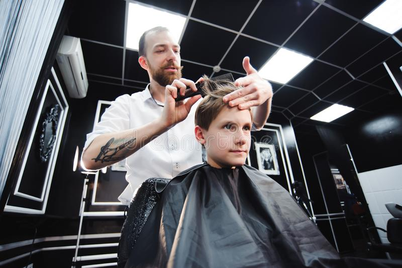 Le maître coupe des cheveux d'un garçon dans le raseur-coiffeur, coiffeur fait la coiffure pour un garçon photos stock