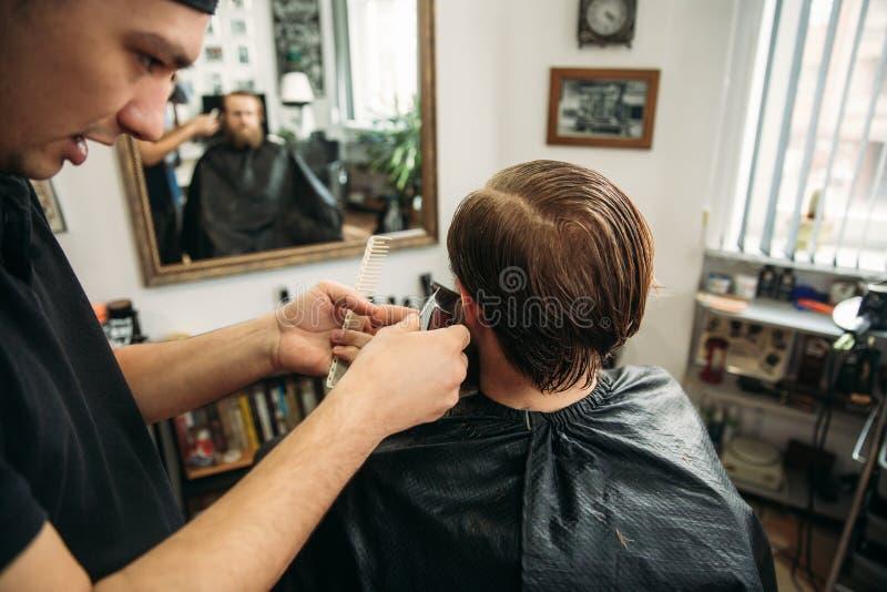 Le maître coupe des cheveux et la barbe des hommes dans le raseur-coiffeur, coiffeur fait la coiffure pour un jeune homme images stock