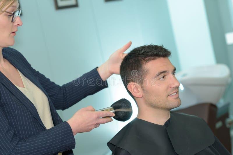 Le maître coupe des hommes de cheveux et de barbe dans le raseur-coiffeur images libres de droits
