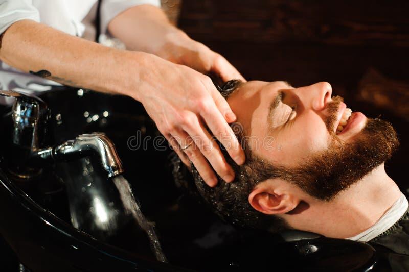 Le maître coupe les cheveux et la barbe des hommes dans le raseur-coiffeur image stock
