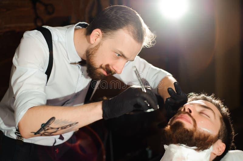 Le maître coupe les cheveux et la barbe des hommes dans le raseur-coiffeur photographie stock