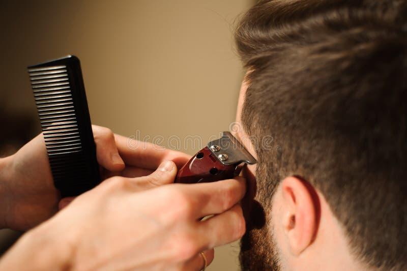 Le maître coupe les cheveux et la barbe des hommes dans le raseur-coiffeur images stock