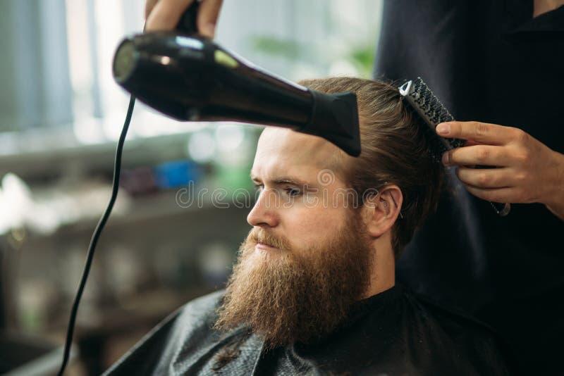Le maître coupe les cheveux et la barbe des hommes dans le raseur-coiffeur et utilise un sèche-cheveux photo libre de droits