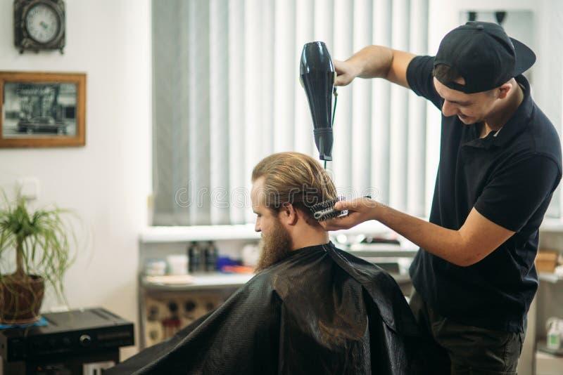 Le maître coupe les cheveux et la barbe des hommes dans le raseur-coiffeur et utilise un sèche-cheveux images stock