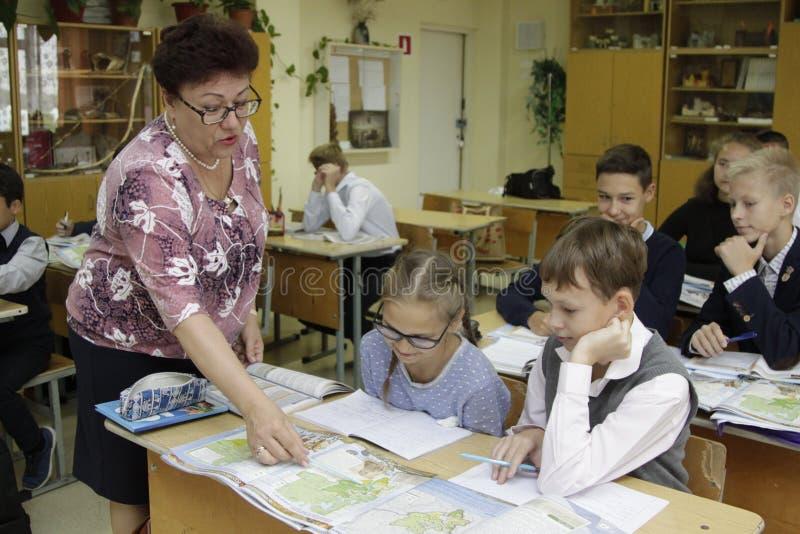 Le maître d'école enseigne des enfants d'école primaire photos stock