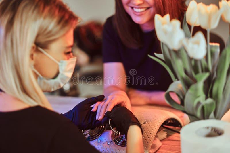 Le maître de clou travaille aux clous de client avec le dossier de clou Le maître porte le masque de protection et les gants no photo stock