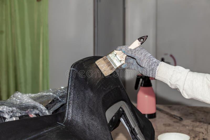 Le maître de la taille de la voiture appliquant la colle avec une brosse sur le panneau en plastique supérieur pour coller le cui image libre de droits