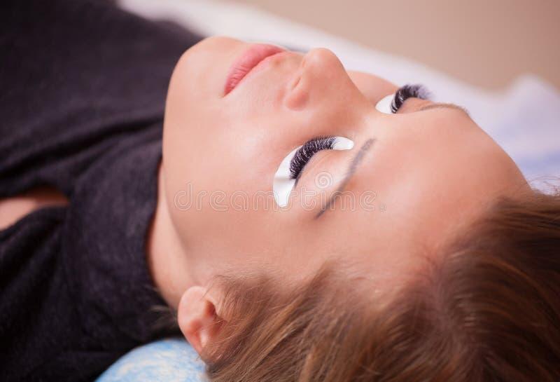 Le maître de maquillage corrige, et renforce des faisceaux de cils, donnant une paire de brucelles dans un salon de beauté images stock
