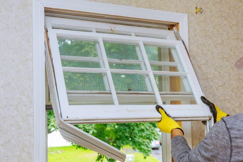 Le maître enlève de vieilles réparations à la maison, fenêtres de rechange photographie stock libre de droits