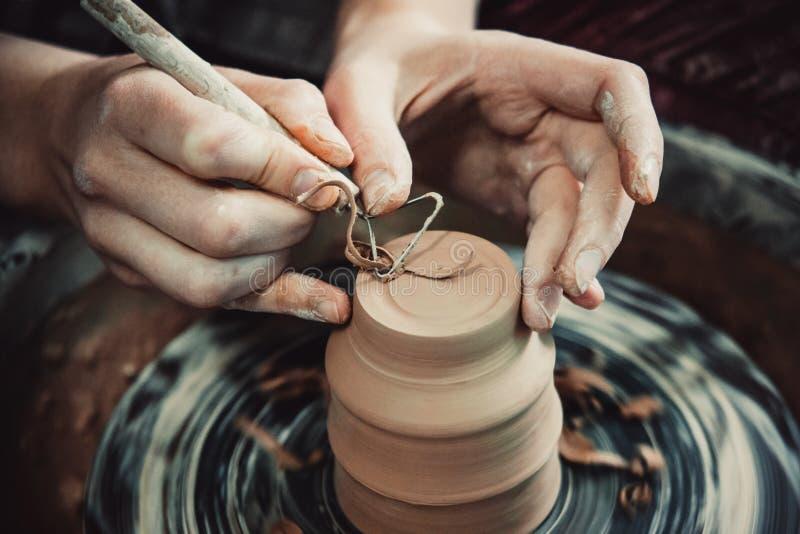 Le maître enlève la couche supérieure d'argile sur le pot avec un outil spécial images stock