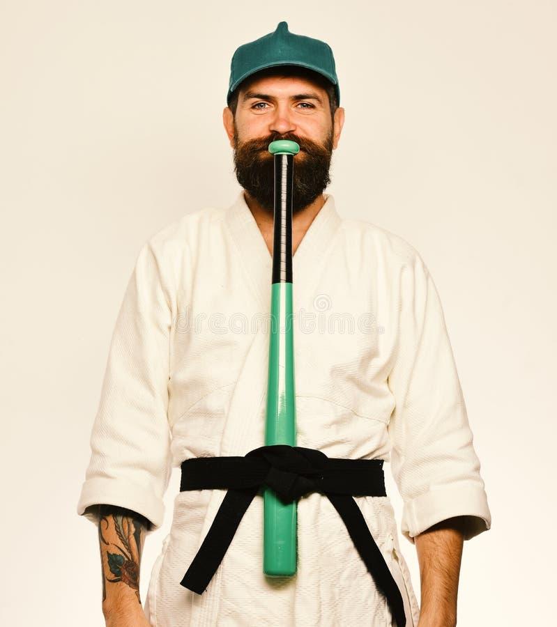 Le maître est prêt pour combattre Concept d'arts martiaux Le joueur de baseball avec le visage heureux met la batte de baseball v photographie stock