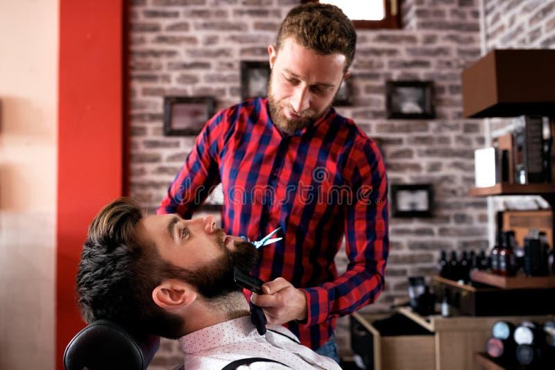 Le maître fait la correction de barbes dans le salon de raseur-coiffeur photos stock