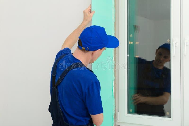 Le maître finisseur fixe les pentes de la fenêtre photos stock