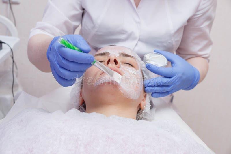 Le maître met un masque blanc avec une brosse sur le visage d'une jeune femme se trouvant sur la table photos stock