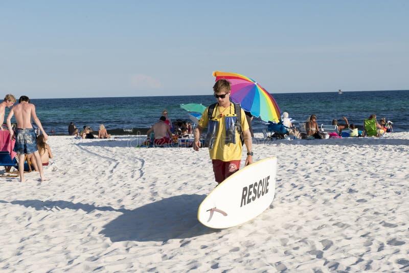 Le maître nageur marche le long de la plage portant une planche de surf de délivrance images libres de droits