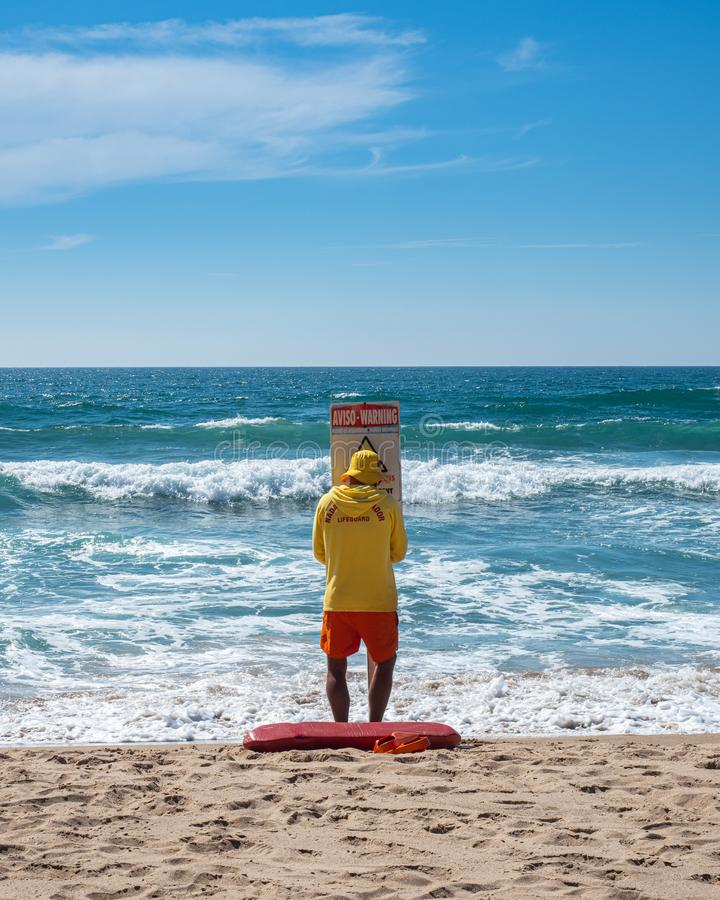Le maître nageur mettant en place un avertissement se connectent la plage photographie stock libre de droits