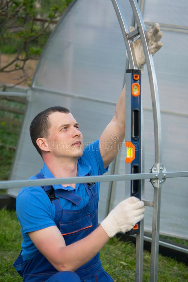 Le maître pour l'installation des serres chaudes, contrôles l'outil de niveau, l'installation correcte du cadre photos libres de droits