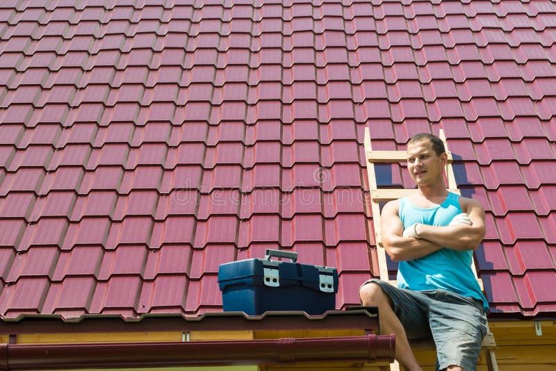 Le maître se repose sur les escaliers contre le toit, l'endroit pour l'inscription photo libre de droits