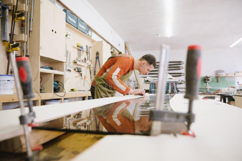 Le maître travaille à une machine de rectification superficielle photos stock