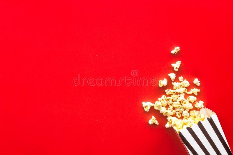 Le maïs éclaté dans le sac de papier a dispersé sur l'espace rouge de copie de vue supérieure de fond photographie stock