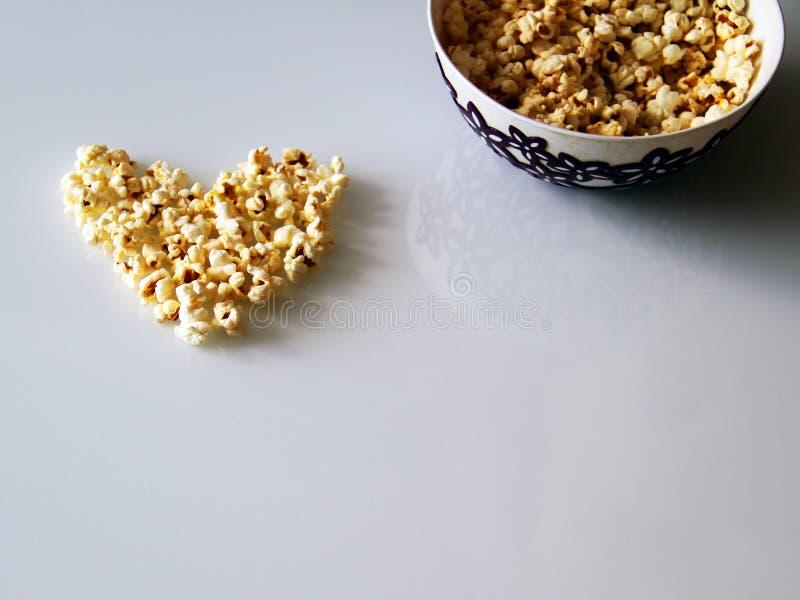 Le maïs éclaté a présenté sous forme de coeur sur un fond blanc photos libres de droits