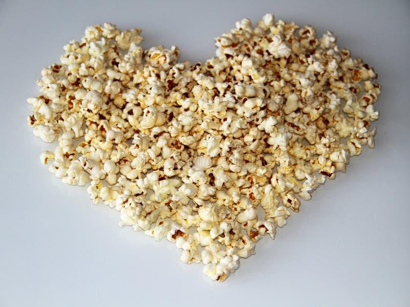 Le maïs éclaté a présenté sous forme de coeur sur un fond blanc image stock