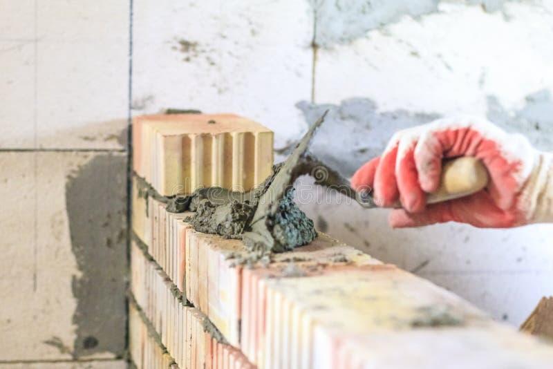 Le ma?tre avec un outil, empile une brique rouge il y a illumination et tonalit? Profondeur de coupe photographie stock libre de droits