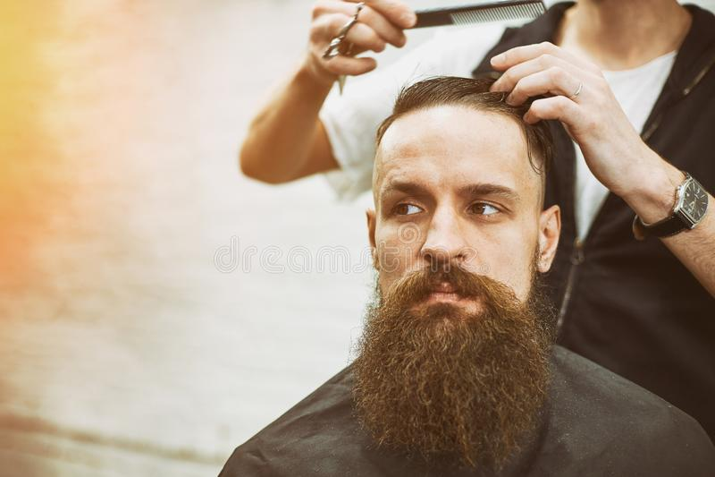 Le ma?tre coupe des cheveux et la barbe des hommes dans le raseur-coiffeur, coiffeur fait la coiffure pour un jeune homme image stock
