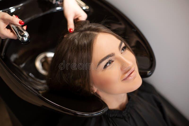 Le ma?tre de coupe de cheveux lave des cheveux de son client a eu images libres de droits