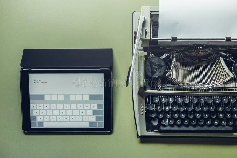 Le macchine da scrivere analogiche e digitali si trovano sulla superficie verde Continuità delle generazioni, concetto di svilupp fotografia stock