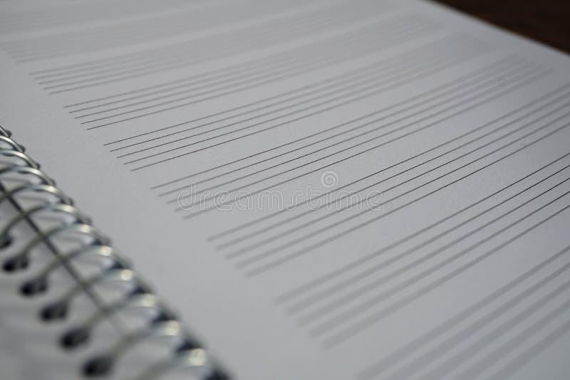 Le macro détail d'un bloc-notes avec le papier rayé comme feuille de piano avec des lignes s'est préparé à la musique de composit photos libres de droits