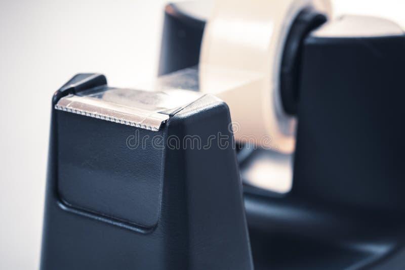 Le macro d'un noir scotchent le support sur un bureau blanc photographie stock