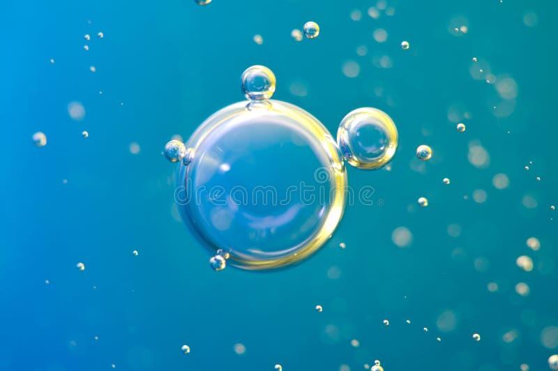Le macro oxygène bouillonne dans l'eau sur le fond bleu photographie stock libre de droits