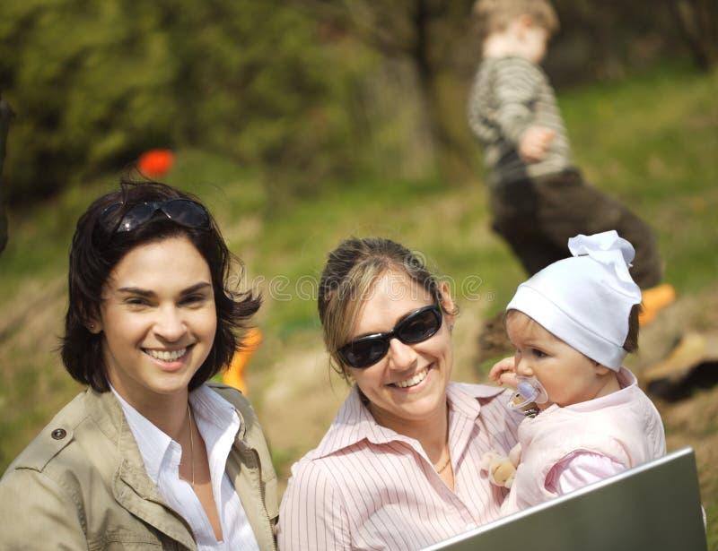 Le madri stanno utilizzando un computer portatile fotografie stock libere da diritti