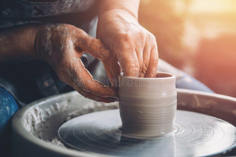 Le magicien froissé de mains sur la roue de potier fait des plats d'argile Endroit ? travailler images stock