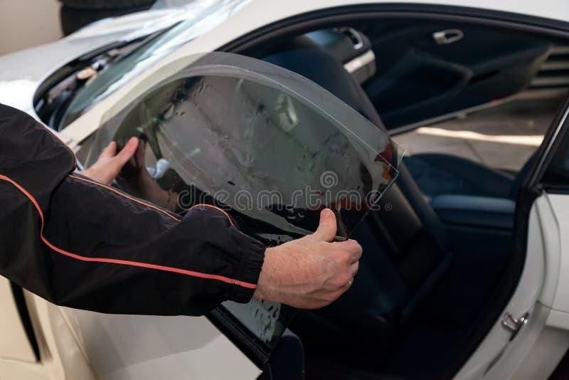 Le magicien pour installer le matériel supplémentaire colle un film de teinte sur le verre avant latéral de la voiture et l'aplat photographie stock