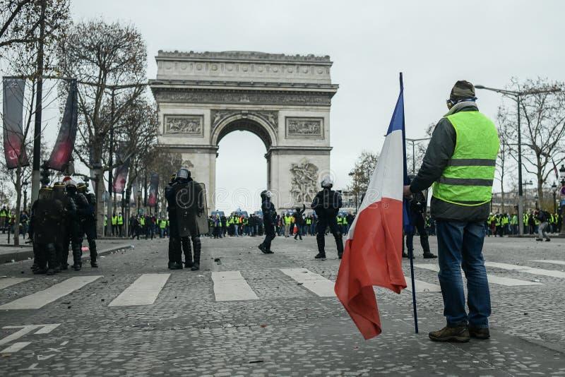 Le maglie gialle - proteste dei jaunes di Gilets - dimostrante che iscena una bandiera francese sta davanti alla polizia di tumul fotografia stock libera da diritti