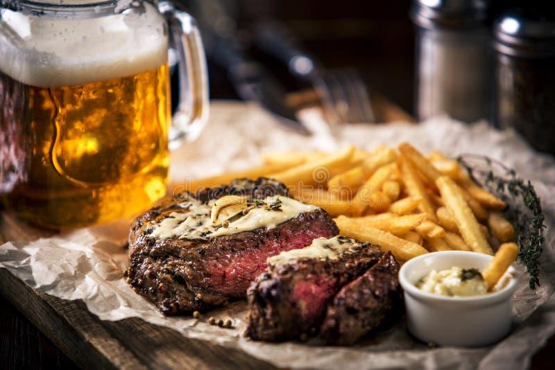 Le maigre sain a grillé le bifteck entre saignant et à point avec des pommes frites, bière photo stock
